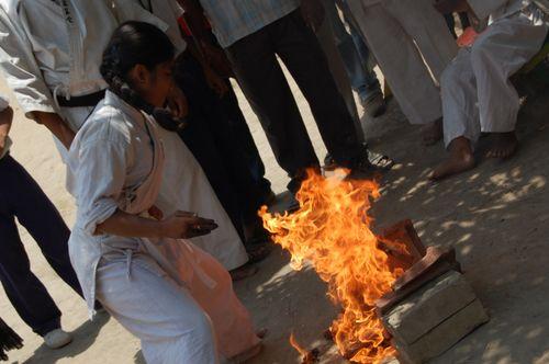 Girl karate chopping bricks on fire with hand