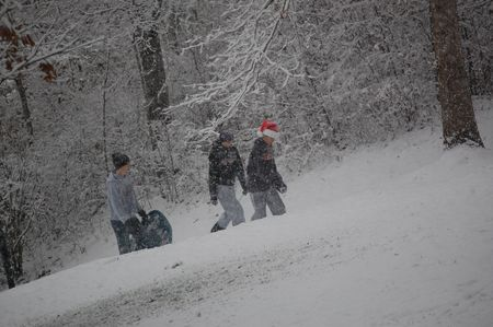 Children walking up snowy driveway
