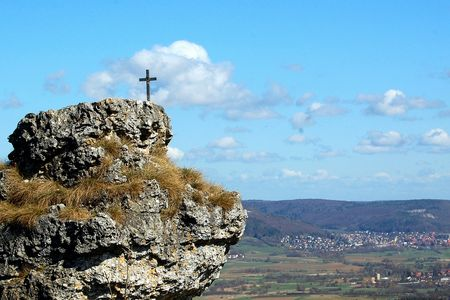 cross on rocky cliff, blue skies and clouds